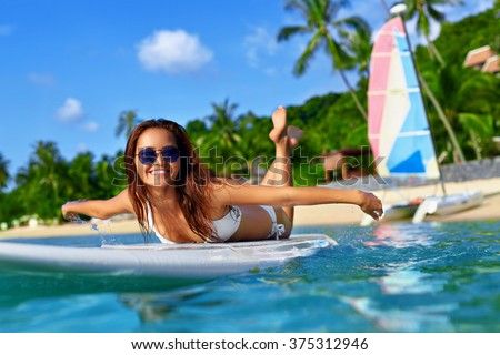 Summer Adventure. Water Sports. Happy Carefree Sexy Woman In Bikini Surfing, Lying On Paddle, Surf Board In Sea At Exotic Resort. Holidays Travel Vacation. Healthy Active Lifestyle. Leisure Activity.  - stock photo