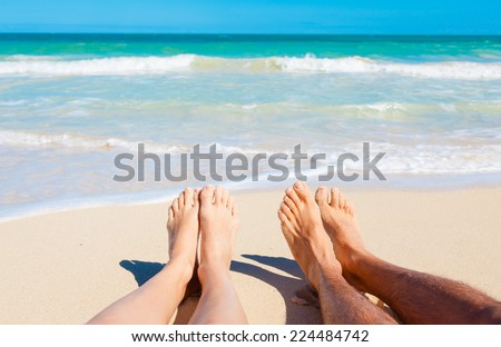 Summer and beach concept - couple lying on the beach - stock photo