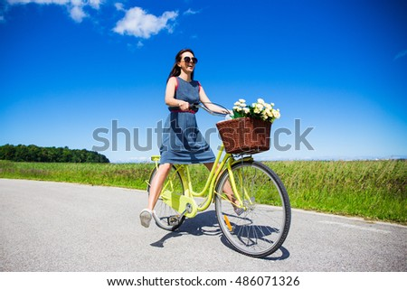 summer and travel concept - happy funny young woman riding on bicycle with raised legs