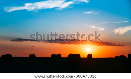 Summer Autumn Field Meadow With Hay Bales Silhouettes Under Sunset Sunbeams. Bright Sky And Dark Ground Panorama. Sun Over Rural Countryside Field At Dawn Or Sunrise Panoramic Background. - stock photo