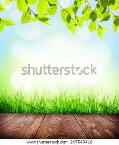 Summer background with wooden floor, green grass and sunlight bokeh - stock photo