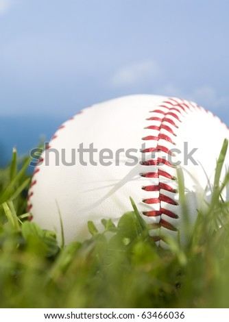 Summer baseball concept with a baseball in the outfield grass against a perfect blue sky. - stock photo