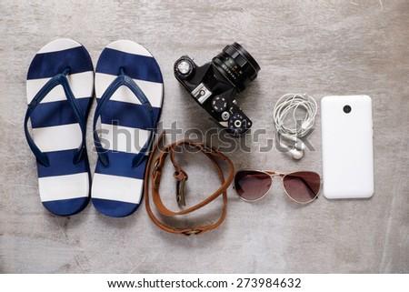 summer beach accessories beach slipper camera strap sunglasses mobile phone earphones - stock photo