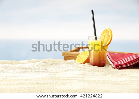summer beach background of sand sun and glass of juice