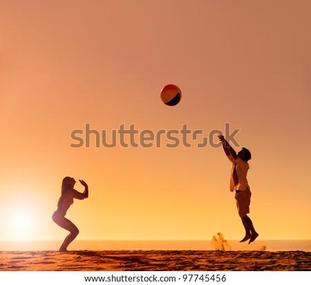 Summer beach ball sunset couple silhouette on the sand having fun - stock photo