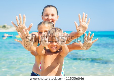 Summer beach - family playing on sandy beach. Focus on the hand