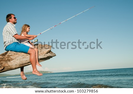 Summer beach, fishing - little girl fishing with father at the beach (space for text) - stock photo