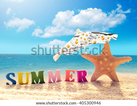 Summer beach. Letters and starfish on a beach sand against the background of the ocean. - stock photo