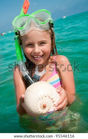 Summer beach - lovely girl diver with seashell in the sea
