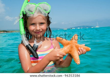 Summer beach - lovely girl diver with starfish in the sea - stock photo
