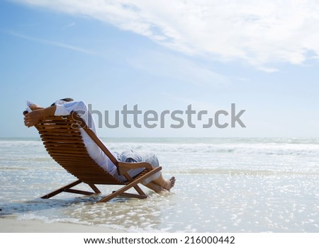 summer beach man sitting and relaxing - stock photo
