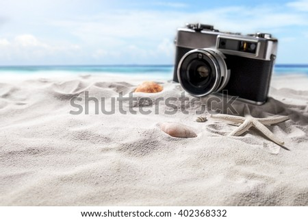 Summer beach. sea shells  and camera on beach side with sunny day blue sky summer concept. - stock photo