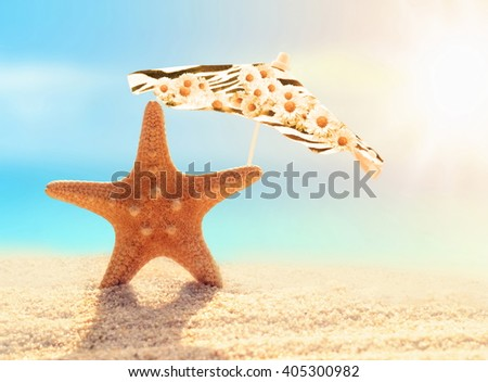 Summer beach. Starfish and umbrella on a beach sand against the background of the ocean. - stock photo