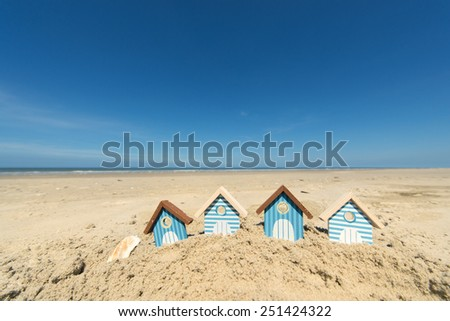 Summer beach with landscape and wooden huts - stock photo