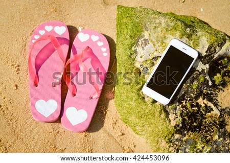 Summer beach with smart phone on sandy and stone rock outdoors background - stock photo