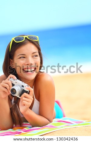 Summer beach woman fun holding vintage retro camera laughing and smiling happy during summer holiday vacation travel. - stock photo