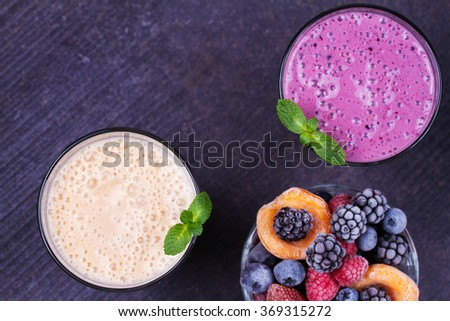 Summer Berries, Apricot and Banana Milkshake Garnished with Mint on Rustic Dark Background. View from Above, Top Shot