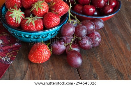 Summer berries in bowls and grapes  on wooden table, fruits, cherry, strawberry - stock photo
