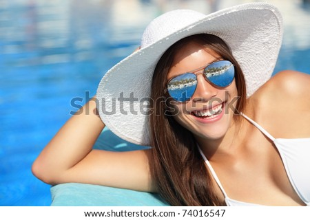 Summer bikini girl smiling by pool. Beautiful young woman wearing beach hat and sunglasses at tropical resort. Beautiful Asian Caucasian female model. - stock photo