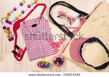 Summer blouse and accessories arranged on the floor. Woman colorful accessories, wicker bag, visor hat, sunglasses and nail polish with striped top. - stock photo