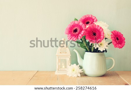 summer  bouquet of flowers and vintage lantern on the wooden table with mint background. vintage filtered image - stock photo