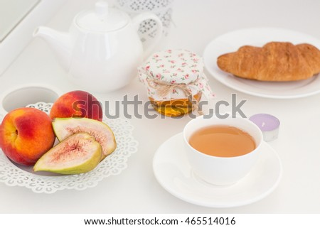 Summer breakfast. Fruit, tea and flowers on a white table.