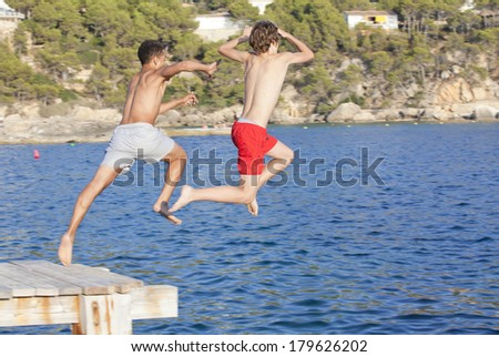 summer camp kids jumping in sea - stock photo