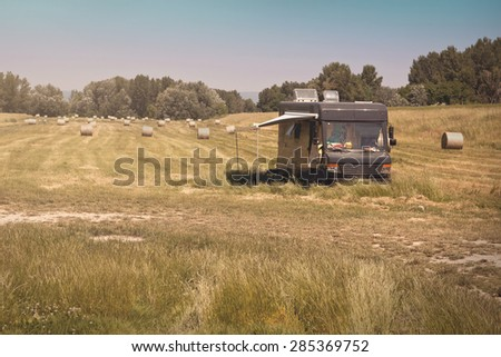 Summer Caravan Parked on Meadow with Hay Bales