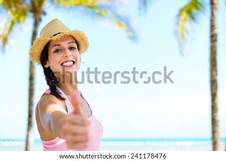 Summer caribbean vacation travel. Successful happy woman doing thumbs up approving gesture on beautiful palm trees and sea background. - stock photo