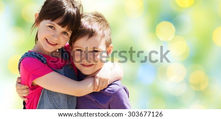 summer, childhood, family, friendship and people concept - two happy kids hugging over green summer lights background - stock photo