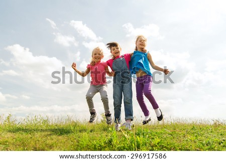 summer, childhood, leisure and people concept - group of happy kids jumping high on green field outdoors