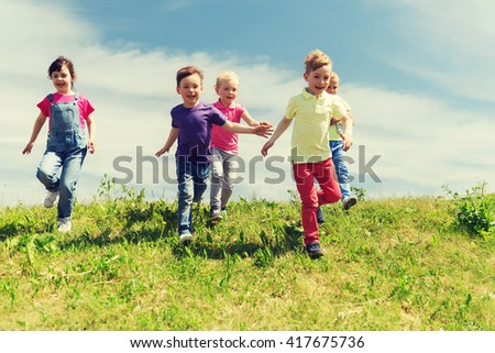 summer, childhood, leisure and people concept - group of happy kids playing tag game and running on green field outdoors - stock photo