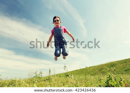 summer, childhood, leisure and people concept - happy little girl jumping high over green field and blue sky outdoors - stock photo