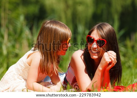 Summer children and happy family concept. Mother and daughter little girl in heart shaped sunglasses, having picnic playing in park outdoors.