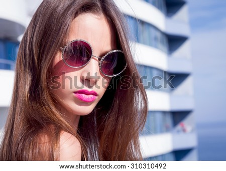 Summer close up fashion portrait Beautiful young woman  standing against blue sea  on sea view balcony with her hair blowing in the breeze,Young woman with pink lipstick and vintage glasses.vacation. - stock photo