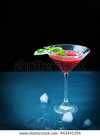 Summer cocktail out of strawberries and alcohol, decorated with basil and served in martini glass, iced cubes, close up, dark background. Vertical, space for text. - stock photo