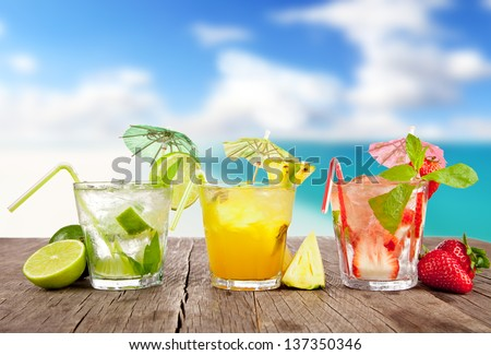 Summer cocktails with pieces of fruit on wooden table. Blur beach on background - stock photo