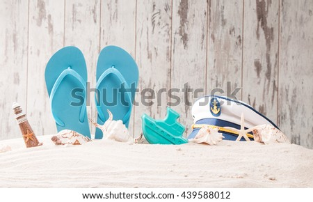 Summer concept, flip-flops, summer accessories in sand with white wooden background - stock photo