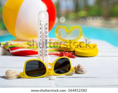 Summer concept of high temperature, flip flop shoes, sunglasses on pier near hotel pool - stock photo