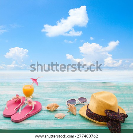 Summer concept of sandy beach, straw hat, shells - stock photo