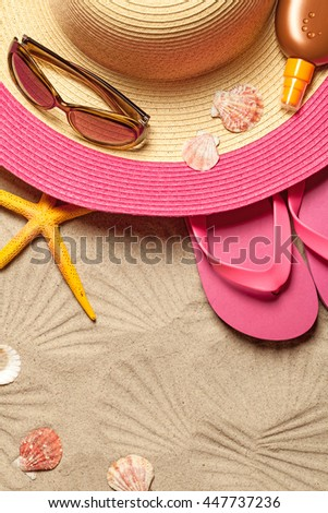 Summer concept with hat, flip flops, shells and sunglasses on sandy beach background. Top view