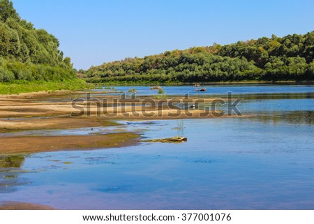 Summer concept with sandy beach, blue river.