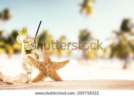 Summer concept with sandy beach, drink, shells and starfish. - stock photo