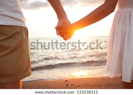Summer couple holding hands at sunset on beach. Romantic young couple enjoying sun, sunshine, romance and love by the sea. Couple on summer vacation travel holiday. - stock photo