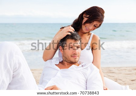 Summer couple smiling laughing on the blue beach - stock photo