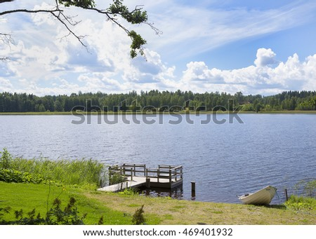 Summer day in Finland. An image of an empty pier on the shore next to a rowing boat. Some tree branches and bushes are in the front. A lake and a forest in the background.