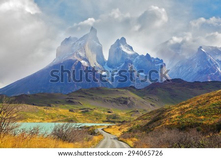 Summer day in the national park Torres del Paine, Patagonia, Chile. A dirt road leads to the cliffs of Los Kuernos - stock photo