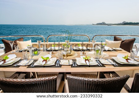 Summer day yacht deck with served table and open sea. - stock photo