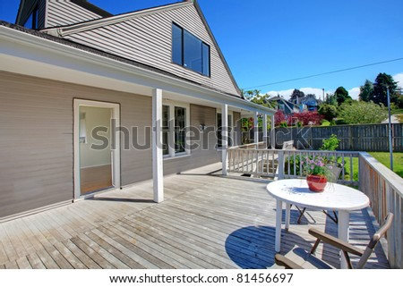 Summer deck of the grey house with railings. - stock photo