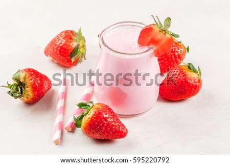 Summer dessert or breakfast - strawberry milkshake with mint, in a small jar, with a striped tubule. On a white table with strawberries, copy space